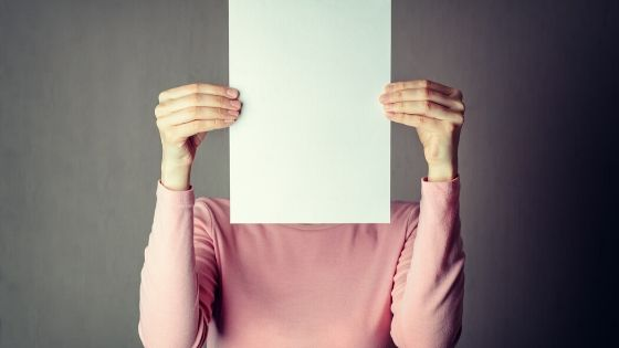 person holding paper in front of their face