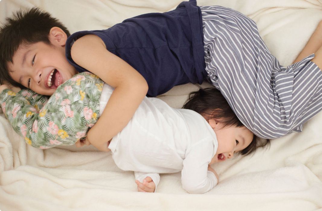 2 kids snuggling on bed